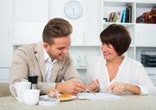 男人和妇女有杯子的咖啡和文件 库存照片