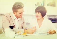 男人和妇女有杯子的咖啡和文件 库存图片