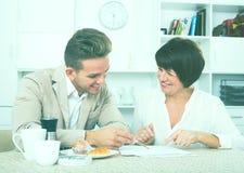 男人和妇女有杯子的咖啡和文件 图库摄影