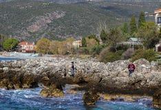 男人和妇女有照相机的在下来岩石由海洋在Kardamyli村庄伯罗奔尼撒半岛的在希腊1 6 2018年 免版税库存照片