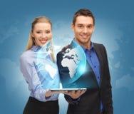 男人和妇女有片剂个人计算机和真正地球的 免版税库存照片