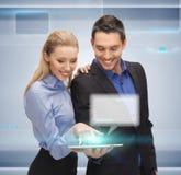 男人和妇女有片剂个人计算机的 免版税库存图片