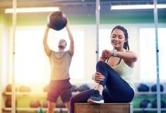 男人和妇女有球的和健身跟踪仪健身房的 库存照片