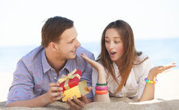 男人和妇女有礼物的在海滩。 免版税图库摄影