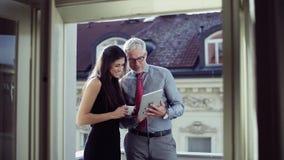 男人和妇女有站立在一个大阳台的片剂的商务伙伴在城市,谈话 股票视频