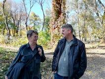 男人和妇女步行在秋天森林里 免版税库存照片