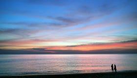 男人和妇女海滩的在日落期间 库存图片