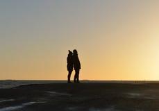 男人和妇女现出轮廓在Uunisaari海岛上的观看的日落 免版税库存图片