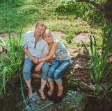 男人和妇女由池塘坐 免版税图库摄影