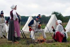 男人和妇女由火坐在Borodino争斗历史再制定在俄罗斯 免版税图库摄影
