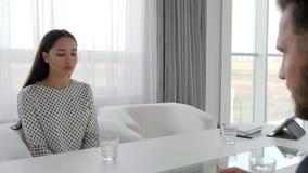 男人和妇女的交谈办公室空间的,凄惨的妇女画象供以座位在桌上在心理治疗家, 股票录像