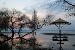 男人和妇女的剪影海滩的以一种衰落为背景在湖 免版税库存图片