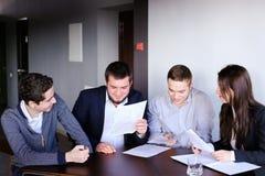 男人和妇女的四个同事为见面聚集在办公室  库存图片