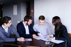 男人和妇女的四个同事为见面聚集在办公室  免版税库存图片