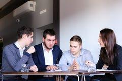 男人和妇女的四个同事为见面聚集在办公室  免版税库存照片