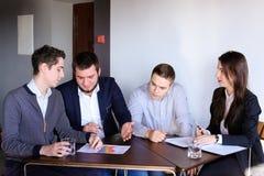 男人和妇女的四个同事为见面聚集在办公室  免版税图库摄影