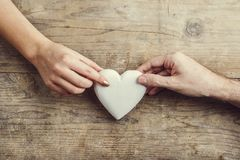 男人和妇女的手通过心脏连接了 免版税库存图片