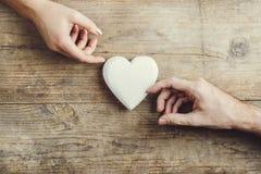 男人和妇女的手通过心脏连接了 库存照片