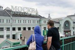 男人和妇女看白俄罗斯语火车站的大厦在莫斯科 免版税图库摄影