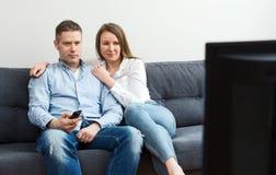 男人和妇女看着电视 免版税库存照片