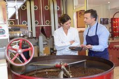 男人和妇女站立了在大桶咖啡豆 免版税库存照片