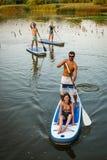 男人和妇女站立paddleboarding 免版税库存图片