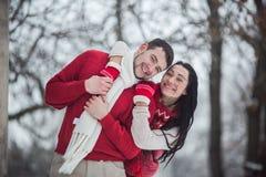 男人和妇女获得乐趣在积雪的公园 免版税库存图片