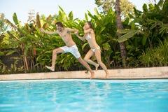 男人和妇女获得跳跃的乐趣在poo 库存图片