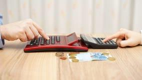 男人和妇女计算热分裂一点金钱,概念  免版税库存照片