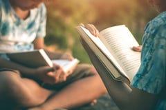 男人和妇女读了在安静的自然的书 库存照片