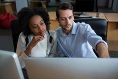 男人和妇女谈论在台式计算机 免版税库存图片