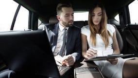 男人和妇女谈论工作文件在出租汽车 免版税库存照片