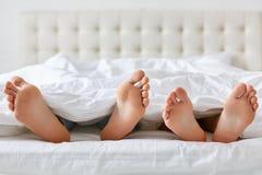 男人和妇女赤脚的图象在毯子下的在卧室 无法认出的丈夫和妻子在舒适的床, enj上花费业余时间 库存图片