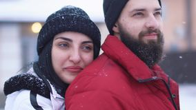男人和妇女身分画象在冬天后院 看愉快的夫妇,女孩拥抱男朋友从后面关闭 股票录像