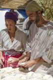 男人和妇女运作的面包在à 维拉的中世纪市场上 免版税库存照片