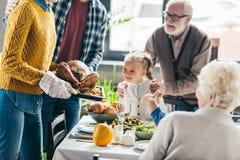 男人和妇女运载的火鸡播种的射击感恩晚餐的,当激动家庭看时 库存照片