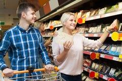 男人和妇女选择在百货商店的乳酪 免版税库存图片