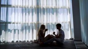 男人和妇女饮用的早晨咖啡剪影在地板上的与自由空间 股票视频