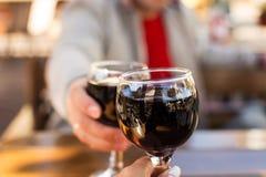 男人和妇女饮用的酒在一个室外咖啡馆的一张桌上 库存图片