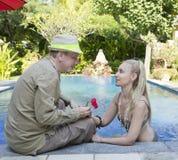 男人和妇女,爱恋的夫妇,在水池在有热带树的一个庭院里 人给妇女一朵花 图库摄影