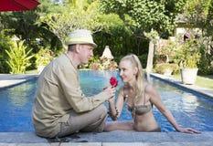 男人和妇女,爱恋的夫妇,在水池在有热带树的一个庭院里 人给妇女一朵花 库存照片