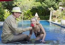男人和妇女,爱恋的夫妇,在水池在有热带树的一个庭院里 人给妇女一朵花 免版税图库摄影