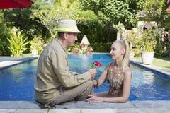 男人和妇女,爱恋的夫妇,在水池在有热带树的一个庭院里 库存照片