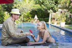 男人和妇女,爱恋的夫妇,在水池在有热带树的一个庭院里 库存图片