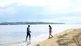 男人和妇女,青年人,获得乐趣和使用在岸,海滩的愉快的结婚的成人夫妇 股票视频