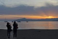男人和妇女whiile亲吻在sestri在日落的levante海滩 免版税库存照片