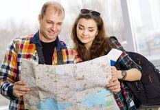 男人和持护照的妇女 看地图,研究的方向 欧洲 会集在一次被引导的游览 蜜月 免版税库存图片