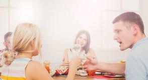男人和白肤金发的妇女在饭桌,党上朋友的 库存图片