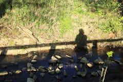 男人或妇女在桥梁,他们的在一个草甸的阴影秋天站立小河的银行的 免版税图库摄影