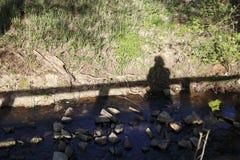 男人或妇女在桥梁,他们的在一个草甸的阴影秋天站立小河的银行的 库存照片